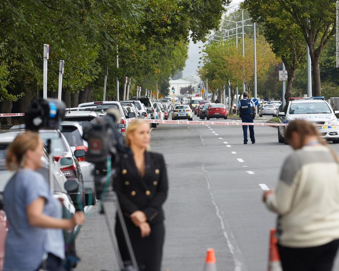 Members of the media wait around the scene as police officers cordon off the area.