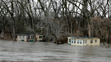 The rising waters of the Elkhorn River south of Arlington, Neb., Thursday, March 14, 2019, floods cabins. Evacuations forced by flooding have occurred in several eastern Nebraska communities. (AP Photo/Nati Harnik)