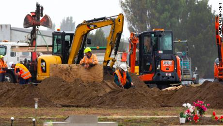 Diggers work behind a white screen fence to dig graves for some of the 50 people who died in Friday's terror attack.