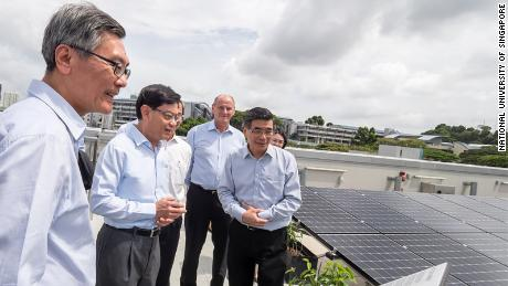 "Visitors view the so-called ""solar farm"" on the building's roof, which contains over 1,200 panels."