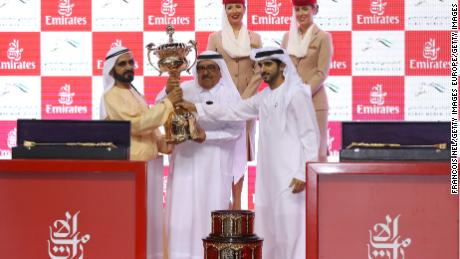 Sheikh Mohammed (L), receives the trophy after his horse Thunder Snow's victory at the Dubai World Cup.