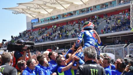 Young pretender Alex Rins held aloft by his team after his victory.