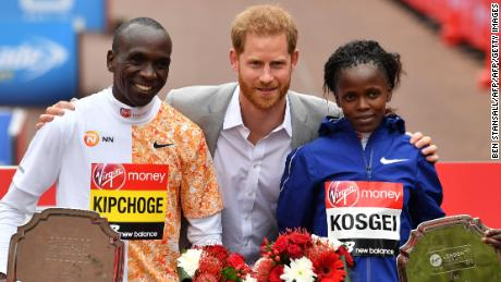 Britain's Prince Harry, Duke of Sussex, is flanked by men's race winner Kenya's Eliud Kipchoge (L) and women's race winner, Kenya's Brigid Kosgei (R) at the medal ceremony at the 2019 London Marathon.