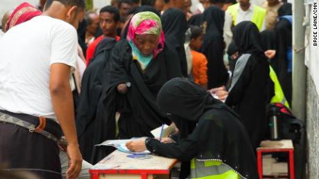Women line up to ask for  international aid in Yemen.