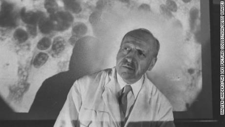 Dr. George Papanicolaou in front of slide of cancer cells at Francis Delafield Hospital.
