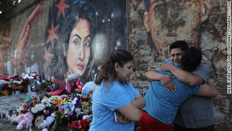 Marlen Ochoa-Lopez's father, Arnulfo Ochoa, gets a surprise hug Wednesday from his 13-year-old son, Oscar, while visiting a mural of his slain daughter painted by Milton Coronado in Chicago.