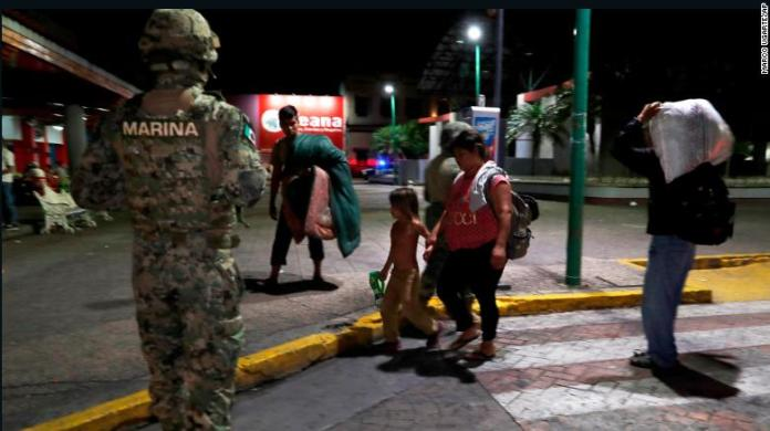 A Mexican marine stands by as camping migrant families are evicted from a park in Tapachula, Mexico, on May 29, 2019.