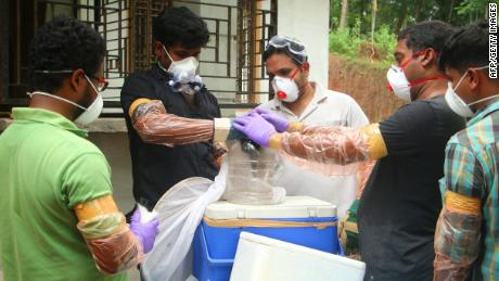 Officials deposit a bat into a container after catching it inside a well at Changaroth in Kozhikode in the Indian state of Kerala on May 21, 2018.