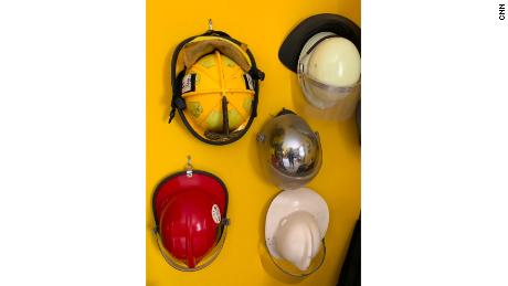 A wall in Scott Phillips-Gartner's home is adorned with firefighter helmets.