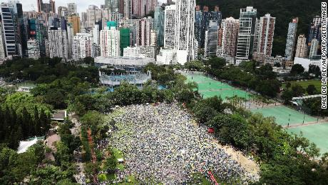 "Protesters waved placards and wore white -- the designated color of the rally. ""Hong Kong, never give up!"" some chanted."