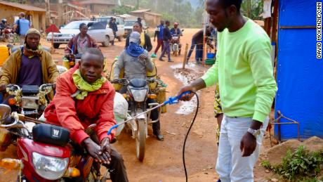 A taxi driver gets his hands washed with a chlorine solution at a checkpoint between Beni and Butembo in Eastern DRC.