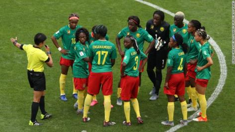 Cameroon players confront referee Qin Liang following England's second goal for Ellen White which is allowed after a VAR decision.