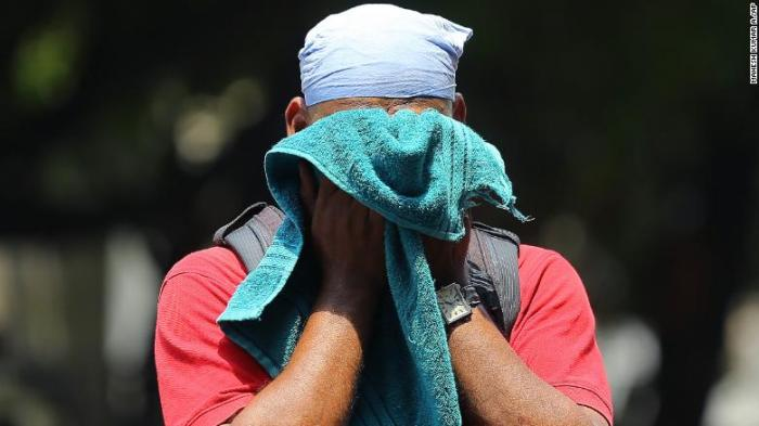 An Indian man uses a towel to wipe the sweat on his face on a hot and humid summer day in Hyderabad, India, on June 3, 2019.