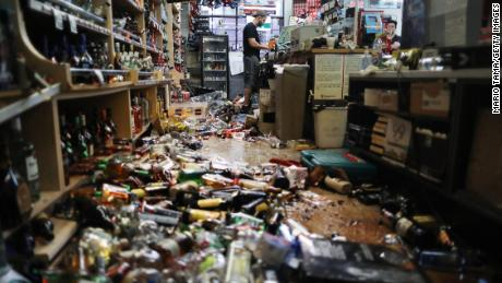 An employee works at the cash register at Eastridge Market, near broken bottles scattered on the floor, following a 7.1 magnitude earthquake, on July 6 in Ridgecrest, California.
