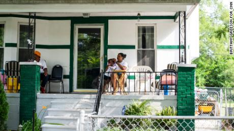 Crystal Daniels and her 3-year-old daughter, Mikayla Daniels, gaze out at passing cars while hanging out on their front porch with Crystal's father, Wayne Daniels, on the city's west side. Wayne has lived in the neighborhood for over 30 years.