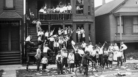 In this 1919 photo provided by the Chicago History Museum, a crowd gathers at a house that has been vandalized and looted during the race riots in Chicago. Some of the crowd is posing inside broken windows, others are standing on the lawn.