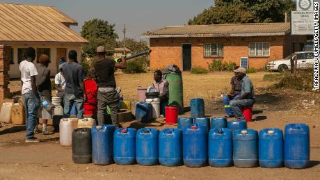 Residents in Harare queue for water.