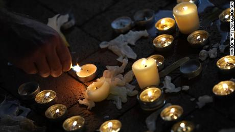 A man tends a makeshift candlelight vigil for Heather Heyer and those who were hurt in Charlottesville, Virginia, in August 2017.