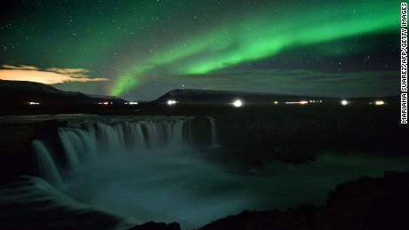 The aurora borealis appear over a waterfall in Iceland.