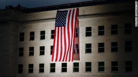 An American flag is unfurled at sunrise at the Pentagon in Washington on the 18th anniversary of the September 11 attacks.