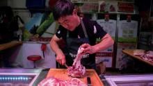 In this picture taken on July 10, 2019, a butcher cuts a piece of pork meat at his stall at a market in Beijing.