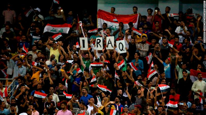 Iraq supporters cheer during the the 2019 WAFF Championship football match between Syria and Iraq in Karbala on August 8, 2019.