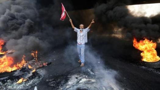 A demonstrator flashes a victory sign as he holds a national flag near a roadblock on October 18.