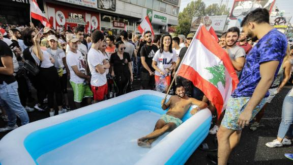A protester holds a Lebanese flag as he sits in an inflatable pool on a highway in the town of Zouk Mosbeh on October 19.