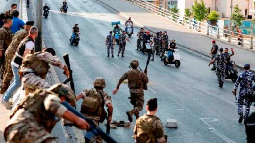 Members of the Lebanese army, left, help intervene between clashing groups of protesters and counter-protesters on a highway in central Beirut.