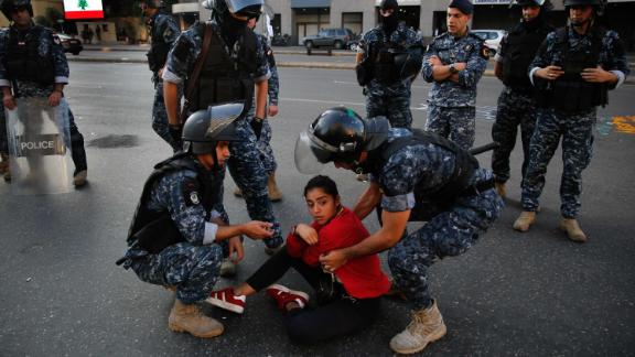 Police move an anti-government protester on Monday.