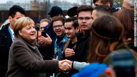German Chancellor Angela Merkel greets young visitors as she walks to the Chapel of Reconciliation before attending the memorial service.