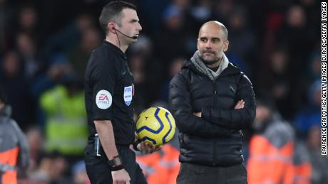 Manchester City manager Pep Guardiola stares pointedly at referee Michael Oliver as he walks out to officiate the second half of the title showdown at Anfield.