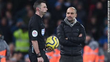 Il Manchester City manager di Pep Guardiola guarda volutamente a arbitro Michael Oliver, come egli cammina per officiare la seconda metà del titolo showdown ad Anfield.