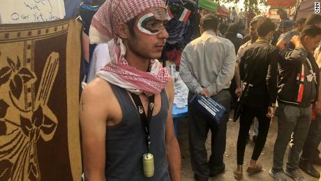 A protester in the tent city has painted the Iraqi flag on his face. He wears a tear gas canister as a medal to show he's not afraid.