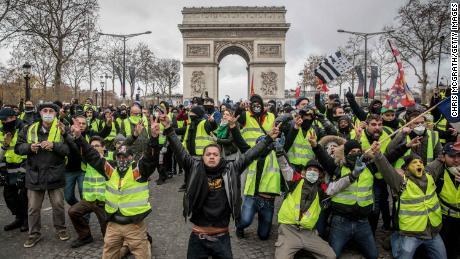 I manifestanti lanciano slogan durante la dimostrazione sugli Champs-Elysées, vicino l'Arco di Trionfo, l ' 8 dicembre, 2018 a Parigi.