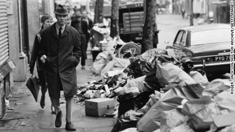 A pedestrian walks past piles of trash during a strike by sanitation workers in 1970.