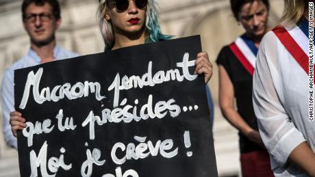 """An activist holds a placard reading """"Macron while you preside I'm dying"""" during a demonstration dedicated to the memory of the women killed by their spouse or ex-spouse since the beginning of the year and against the violence against women, in front of the Paris city hall, on August 28."""