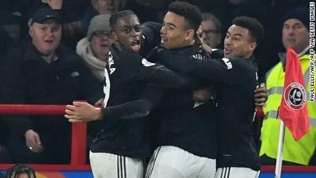 Marcus Rashford, who is hidden, celebrates with teammates after scoring Manchester United's third goal.