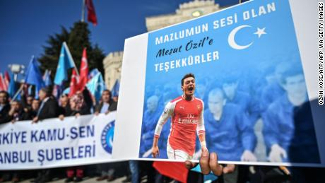 "A supporter of China's Muslim Uighur minority holds a placard of Arsenal's Turkish origin German midfielder Mesut Ozil reading ""Thanks for being our voice"" past flags of East Turkestan during a demonstration at Beyazid square in Istanbul on December 14, 2019. - Arsenal's Mesut Ozil, a German footballer of Turkish origin, expressed on December 14, 2019 support for Uyghurs in Xinjiang and criticised Muslim countries for their failure to speak up for them."
