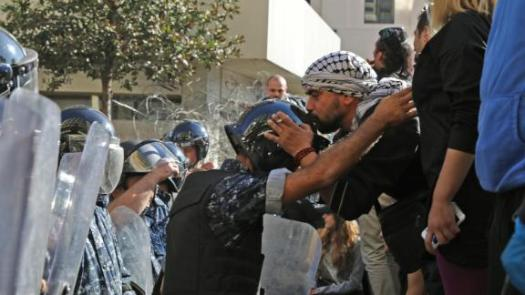 A Lebanese protester kisses the helmet of a riot policeman on November 19 near the parliament headquarters in Beirut.