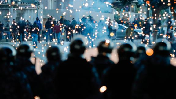 Supporters of Lebanon's Shiite Hezbollah and Amal groups throw fireworks towards Lebanese riot police during clashes on December 14 in Beirut.