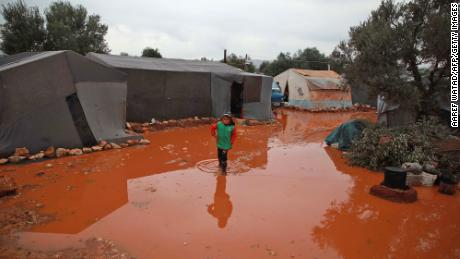 A girl walks through a rainwater puddle before tents in a flooded camp for displaced Syrians near the village of Killi in northwestern Idlib province on December 5, 2019.