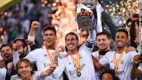 Real Madrid captain Sergio Ramos raises the trophy after scoring the winning penalty.