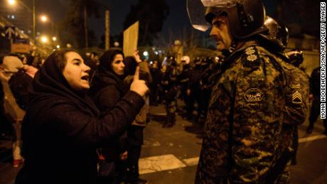 A woman attending a candlelight vigil for the victims of the Ukraine International Airlines crash, talks to a policeman following the gathering in front of the Amirkabir University in Tehran.