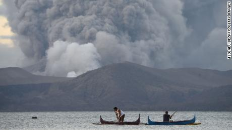 Residents living along Taal lake catch fish as Taal volcano erupts in Tanauan town.