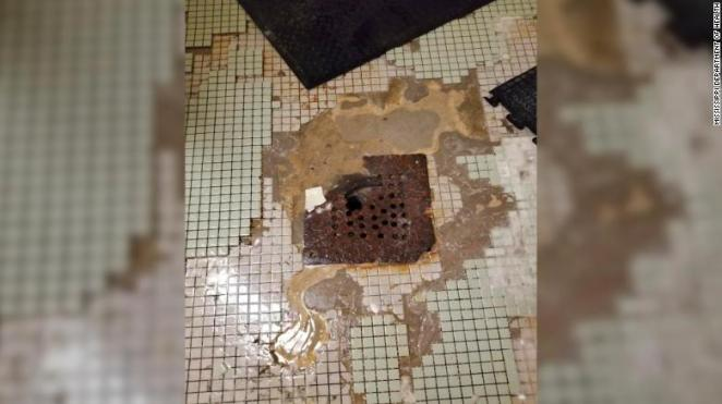 The inspector cited problems with showers, including leaks, missing knobs and this rusty drain.