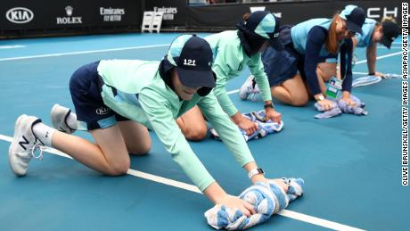 Staff clean dirt off the outside courts at Melbourne Park