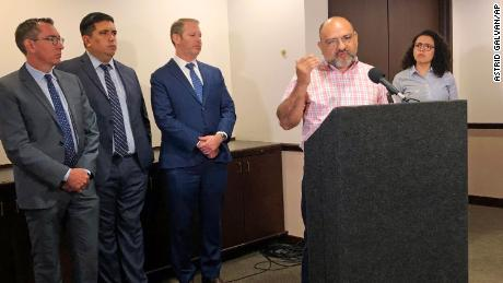 Pastor Angel Campos, at the podium in June 2019, said he felt afraid after the two groups protested at his church over its aiding of  families who had recently arrived at the southern border.
