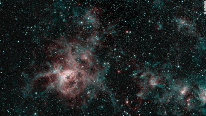 NASA's Spitzer Space Telescope captured the Tarantula Nebula in two wavelengths of infrared light. The red represents hot gas, while the blue regions are interstellar dust.