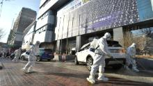 Workers from a disinfection service company disinfect a street in front of a branch of the Shincheonji religious group in Daegu, South Korea, on February 19.